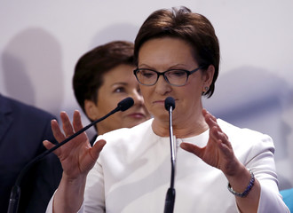 Poland's Prime Minister Kopacz adjusts the microphones as she arrives to speak to supporters following the announcement of the official results of Sunday's election in Warsaw