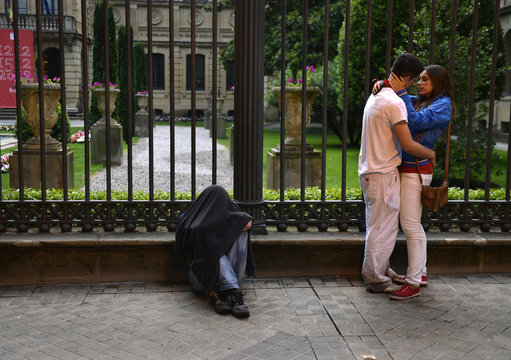 A man sleeps with his jacket over his head next to a couple kissing at the San Fermin festival in Pamplona