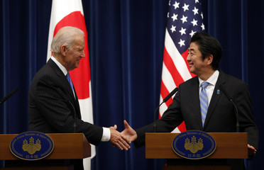 U.S. Vice President Joe Biden and Japan's Prime Minister Shinzo Abe reach out to shake hands at the end of their joint news conference following their meeting at the prime minister's official residence in Tokyo