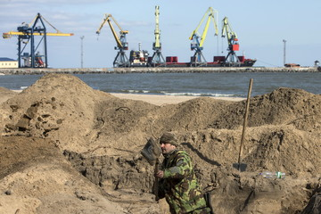 A Ukrainian serviceman digs trenches on a beach in the port city of Mariupol on the Azov Sea