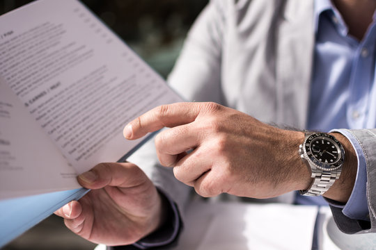 Male Hand Holding Restaurant Menu to Make Order for Lunch