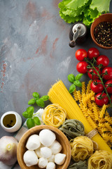 Raw ingredients of Italian pasta, spaghetti, tagliatelle, fusilli, garlic, basil, mozzarella,  pepper, cherry tomatoes and olive oil on gray  background. Selective focus.Top view. Copy space.