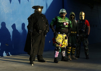 Members of the Xtreme Justice League, Midnight Highwayman, Mr. Xtreme, Light Fist and Spartan  pose for a picture while on patrol at a local street fair in San Diego