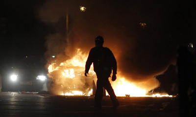 A police officer wearing riot gear walks past a burning police car in Tottenham
