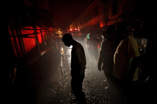 Onlooker is silhouetted by the light of a firetruck after a fire at Comayaguela market in downtown Tegucigalpa