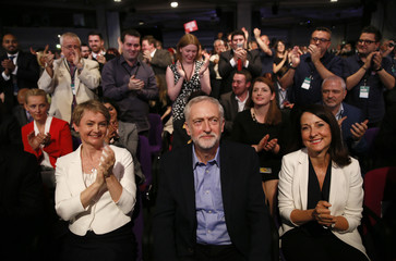 Labour leadership candidates Yvette Cooper (L) and Liz Kendall (R) applaud new leader Jeremy Corbyn (C), at the Queen Elizabeth Centre in central London