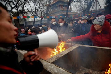 A man uses a megaphone to give instructions as people burn incense sticks and pray for good fortune at Yonghegong Lama Temple on the first day of the Lunar New Year of the Rooster in Beijing