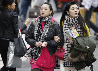 Tourists walk as they shop in central Seoul