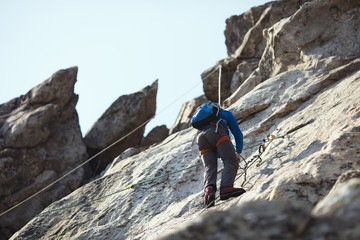 A rock climber climbs the wall in the mountains.