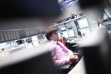 A trader looks at screens at the Frankfurt stock exchange