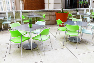 Outdoor empty cafe at city street with chairs and table