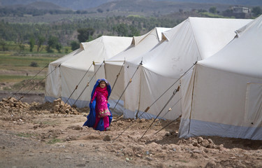 A girl, whose family displaced by military operation last year against militants in Bara, walks near makeshift tents wearing a burqa at the United Nations High Commission for Refugees supported Jalozai camp