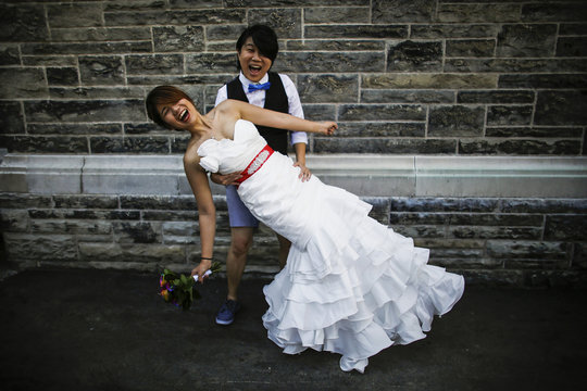 """A couple poses for a picture before taking part in """"The Celebration of Love"""", a grand wedding where over 100 LGBT couples will get married, at Casa Loma in Toronto"""