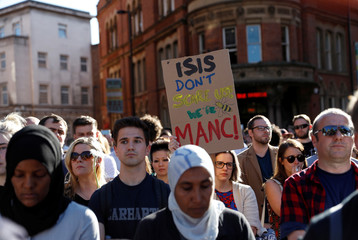 A woman holds a placard as people take part in a vigil for the victims of an attack on concert goers at Manchester Arena, in central Manchester