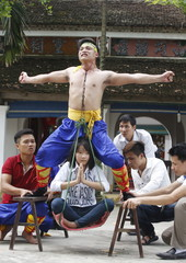 Nguyen Manh Quan carries a girl using his throat area as he performs during a showcase of the traditional Thien Mon Dao kung fu in Du Xa Thuong