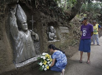Sculptor looks as woman offers bouquet of flowers at image of Pope John Paul II which he and brother Oca carved on hillside in Maragundon town