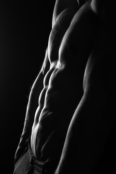 Sexy Athletic Male Model with Perfect Six Pack Abs on Black Background
