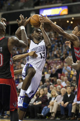 Sacramento Kings' Tyreke Evans drives to the basket between Toronto Raptors' Mickael Pietrus of France and Amir Johnson during the second half of their NBA basketball game in Sacramento