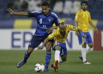 Youssef El-Arabi of Saudi Arabia's Al-Hilal fights for the ball with Hamed Shami of Qatar's Al-Gharafa during their AFC Champions League soccer match in Doha