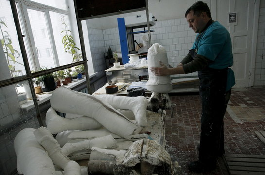 An employee works on a prosthetic leg at the Orthopedic Center in Donetsk