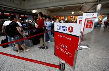 Passengers wait in line at a Turkish Airlines (THY) counter at the international departure terminal of the Ataturk airport in Istanbul