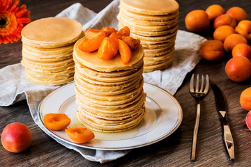 Stackes of homemade american pancakes served with honey and apricots on wooden background