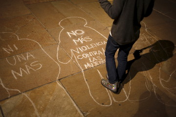 """A girl stands over chalk figures of women drawn on the floor after taking part in a performance entitled """"Women in Black"""" in Malaga"""
