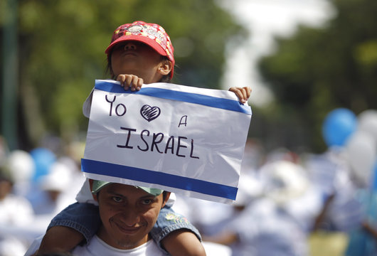 """A girl holds up a sign reading, """"I love Israel"""" during a demonstration supporting Israel's military action in the Gaza strip, in Guatemala City"""