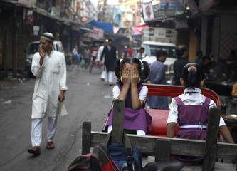 A school girl reacts to the camera as she sits on a rickshaw on her way to school in the old quarters of Delhi