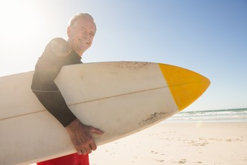 Portrait of smiling senior man holding surfboard