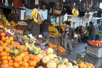 Residents pick fruits at a market in Aleppo's al-Shaar neighbourhood, Syria