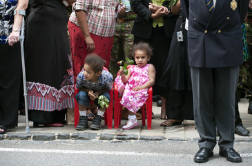 Children sit on small chairs as the repatriation cortege carrying Corporal Rogoiruwai, Kingsman Tagitaginimoce and Trooper Smith passes through Wootton Bassett