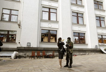 Armed and masked pro-Russian activist talks with woman at seized regional government headquarters in Luhansk, eastern Ukraine