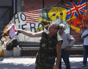 A picture of a British flag is set on fire during a protest at Buenos Aires cruise ship terminal