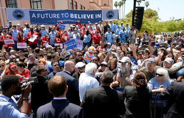 U.S. Democratic presidential candidate Bernie Sanders works the crowd as a supporter holds up a look-a-like puppet at a rally in San Pedro