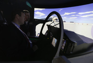 A visitor is briefed on a flight simulator at the  Bahrain International Airshow held at the Sakhir Air Base, south of Manama