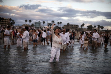 Rabbi Naomi Levy throws bread crumbs into the Pacific Ocean at the Nashuva Spiritual Community Jewish New Year celebration on Venice Beach in Los Angeles