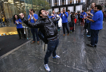 A customer celebrates outside the Apple Store in New York after being the first to buy the new Apple iPad Air