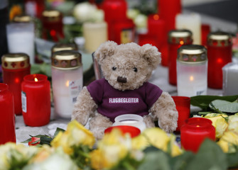 "A teddy bear wearing a shirt with the word ""flight attendant"" is placed outside the Germanwings headquarters at Cologne Bonn"