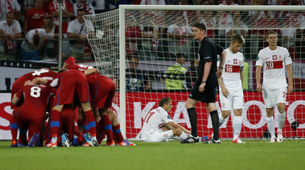 Poland's players react as Czech Republic's players celebrate a goal during their Group A Euro 2012 soccer match at the City stadium in Wroclaw