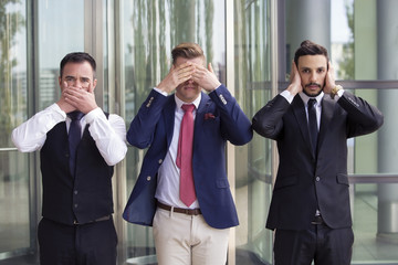 handsome businessmen as the three wise monkeys