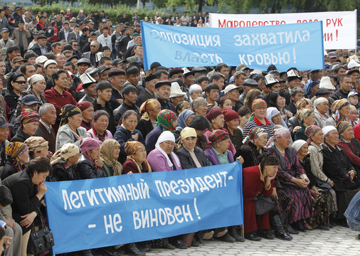 Supporters of the ousted President Kurmanbek Bakiyev hold posters at a rally in the centre of Jalalabad