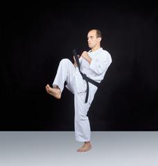 Sportsman is beating blow knee in karategi