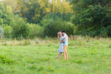 Couple embracing on the countryside. Young romantic man and woman standing and hugging each other with tenderness on nature. Young love concept.