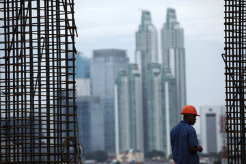 A worker stands next to steel rods at a construction site of Kuningan City super block in Jakarta