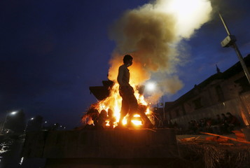 A man walks next to the burning pyre of a family member, who died in Saturday's earthquake, during the cremation along a river in Kathmandu