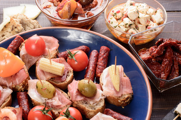 Appetizers with prosciutto ham on blue plate