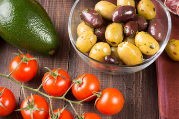 Olives, avocado and tomatoes on wooden table