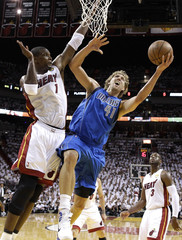 Dallas Mavericks' Nowitzki of Germany shoots past Miami Heat's Bosh during the first quarter in Game 1 of the NBA Finals basketball series in Miami
