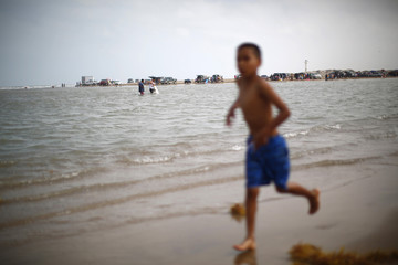 A boy runs on the shore at the boundary between the United States and Mexico, where the Rio Grande river meets the Gulf of Mexico, in Brownsville, Texas